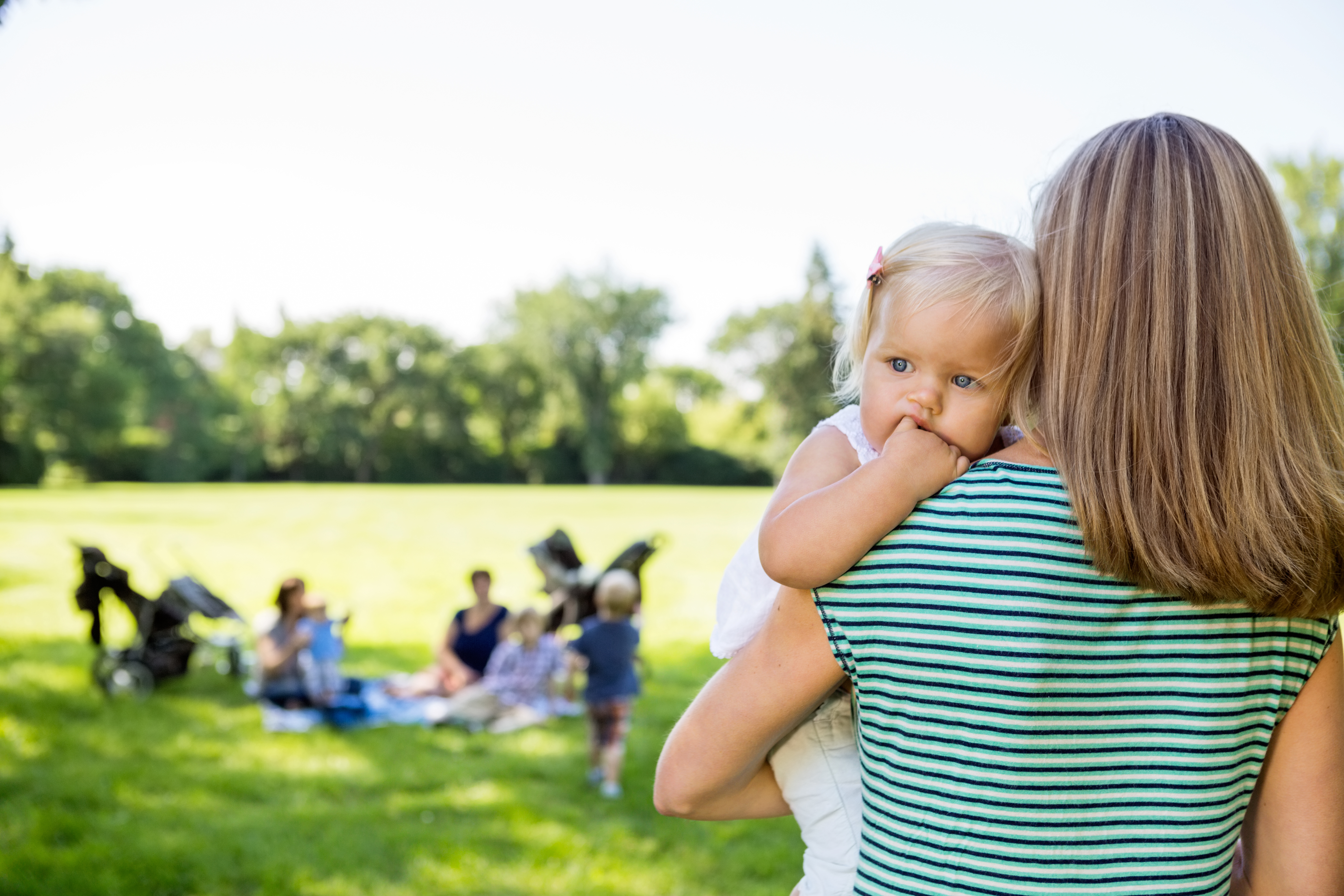 Mother Carrying Daughter Looking Away In Park